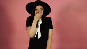 Retrato da jovem mulher chocada na roupa leve que olha a câmera, cobrindo a boca com as palmas isoladas no fundo cor-de-rosa filme