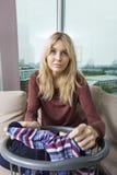 Retrato da jovem mulher com a cesta de lavanderia que senta-se no sofá em casa fotos de stock