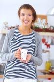 Retrato da jovem mulher com o copo contra a cozinha Fotos de Stock Royalty Free