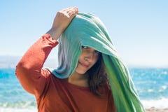 Retrato da jovem mulher com o lenço do verde longo na cabeça na praia com fundo do mar Fotografia de Stock