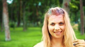 Retrato da jovem mulher com pó colorido em seus sorrisos do cabelo louro na câmera filme
