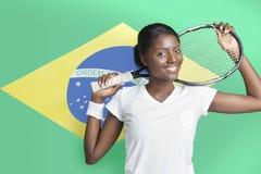 Retrato da jovem mulher com a raquete de tênis contra a bandeira brasileira fotografia de stock royalty free