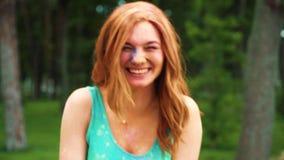 Retrato da jovem mulher de cabelo vermelha que ri da câmera coberta com o pó de Holi filme