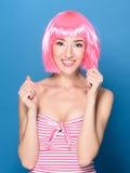 Retrato da jovem mulher de sorriso bonita com cabelo cor-de-rosa em um fundo azul fotos de stock