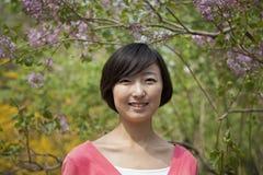 Retrato da jovem mulher de sorriso com cabelo médio do comprimento fora no parque na primavera Imagens de Stock Royalty Free