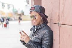 Retrato da jovem mulher de sorriso com fones de ouvido e da música de escuta do telefone esperto na rua foto de stock royalty free