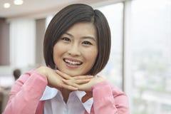 Retrato da jovem mulher de sorriso com mãos sob seu Chin, olhando a câmera Imagem de Stock Royalty Free
