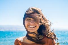Retrato da jovem mulher de sorriso feliz no fundo da praia e do mar Jogos do vento com cabelo longo da menina Imagens de Stock