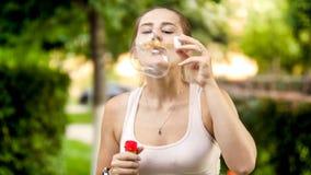 Retrato da jovem mulher de sorriso feliz que funde bolhas de sabão coloridas no parque do verão foto de stock royalty free