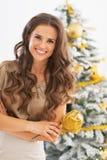 Retrato da jovem mulher de sorriso na frente da árvore de Natal foto de stock royalty free