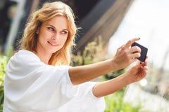 Retrato da jovem mulher de sorriso que faz a foto do selfie no parque fotografia de stock