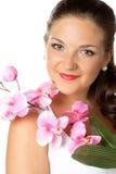Retrato da jovem mulher e do orhid cor-de-rosa no branco fotografia de stock