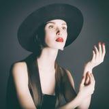 Retrato da jovem mulher em um chapéu negro Fotos de Stock