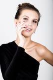 Retrato da jovem mulher em um vestido preto, guardando as mãos perto da cara, surpreendeu Fotos de Stock