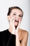 Retrato da jovem mulher em um vestido preto, guardando as mãos perto da cara, surpreendeu Fotos de Stock Royalty Free