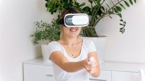 Retrato da jovem mulher entusiasmado que joga o jogo do atirador no capacete de VR foto de stock