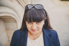 Retrato da jovem mulher excesso de peso bonita de sorriso feliz na obscuridade - casaco azul fora na rua Jovem mulher gorda segur Fotos de Stock Royalty Free