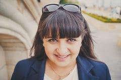 Retrato da jovem mulher excesso de peso bonita de sorriso feliz na obscuridade - casaco azul fora na rua Jovem mulher gorda segur Imagem de Stock