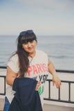Retrato da jovem mulher excesso de peso bonita de sorriso feliz no t-shirt branco e da obscuridade - casaco azul fora na rua conf Imagens de Stock Royalty Free