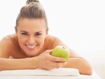 Retrato da jovem mulher feliz com a maçã que coloca na tabela da massagem Imagem de Stock