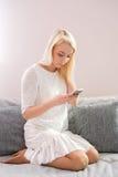 Retrato da jovem mulher feliz com o telefone celular que senta-se no sofá em casa Imagem de Stock Royalty Free