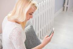 Retrato da jovem mulher feliz com o telefone celular que senta-se no sofá em casa Fotos de Stock Royalty Free