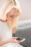 Retrato da jovem mulher feliz com o telefone celular que senta-se no sofá em casa Foto de Stock