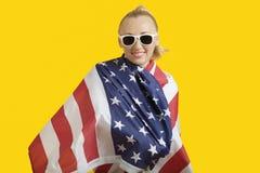 Retrato da jovem mulher feliz envolvido na bandeira americana sobre o fundo amarelo Fotografia de Stock Royalty Free