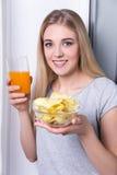 Retrato da jovem mulher feliz que come microplaquetas e que bebe o suco Fotografia de Stock Royalty Free
