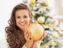 Retrato da jovem mulher feliz que guarda a bola do Natal Imagens de Stock