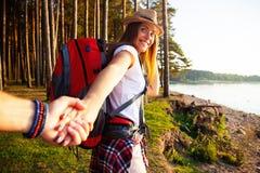 Retrato da jovem mulher feliz que guarda a mão de seu noivo ao andar na floresta foto de stock