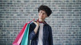 Retrato da jovem mulher feliz que guarda os sacos de compras de papel que olham a câmera filme