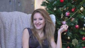 Retrato da jovem mulher feliz que sorri perto da árvore de Natal vídeos de arquivo
