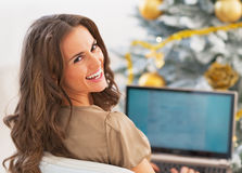 Retrato da jovem mulher feliz que usa o portátil perto da árvore de Natal fotografia de stock
