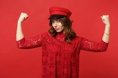 Retrato da jovem mulher forte atrativa no vestido e no tampão do laço que mostram os músculos do bíceps na parede vermelha brilha fotos de stock royalty free