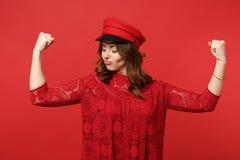 Retrato da jovem mulher forte engraçada no vestido e no tampão do laço que mostram o bíceps, músculos isolados na parede vermelha imagem de stock royalty free