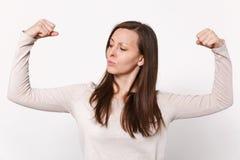 Retrato da jovem mulher forte na roupa leve que mostra, olhando de lado no bíceps, músculos isolados na parede branca imagens de stock royalty free