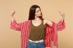 Retrato da jovem mulher forte na roupa ocasional que espalha as mãos, mostrando o bíceps, músculos isolados no bege pastel imagem de stock