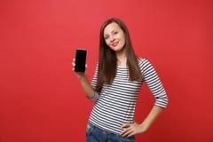 Retrato da jovem mulher impressionante em roupa listrada que guarda o telefone celular com a tela vazia preta da placa isolada so imagem de stock royalty free