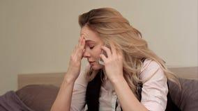 Retrato da jovem mulher infeliz que faz o telefonema irritado em casa fotos de stock