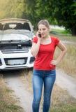 Retrato da jovem mulher irritada que chama o serviço do carro na estrada do campo Fotografia de Stock Royalty Free