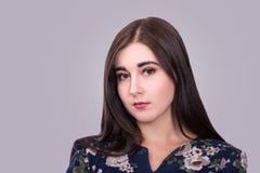 Retrato da jovem mulher lindo no fundo cinzento fotografia de stock royalty free