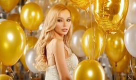 Retrato da jovem mulher loura entre balões e a fita dourados Fotos de Stock Royalty Free