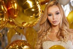 Retrato da jovem mulher loura entre balões e a fita dourados Imagens de Stock