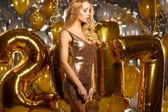 Retrato da jovem mulher loura entre balões e a fita dourados Fotografia de Stock