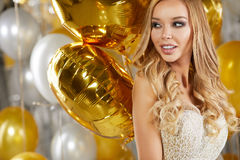 Retrato da jovem mulher loura entre balões e a fita dourados Fotos de Stock