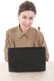 Retrato da jovem mulher na camisa que senta e que usa o portátil Imagem de Stock Royalty Free