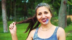 Retrato da jovem mulher no pó do festival de Holi que sorri na câmera video estoque