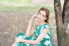 Retrato da jovem mulher no parque no vestido verde imagens de stock royalty free
