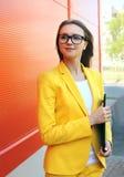 Retrato da jovem mulher nos vidros, terno amarelo com dobrador Imagens de Stock
